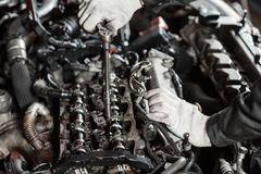 Repairing of modern diesel engine, workers hands and tool. Close-up of an auto mechanic working on a car motor.  Stock Photos