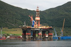 Repairing oil platform. An oil platform parked in a fjord for repairing Royalty Free Stock Photo
