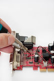 Repairing old graphica PCI card with soldering iron Royalty Free Stock Image