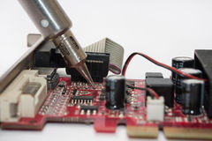Repairing old graphica PCI card with soldering iron Stock Image