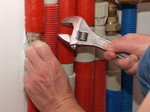 Repairing the pipes. Men hands with spanner repairing pipes in boiler room Royalty Free Stock Photography