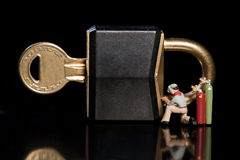 Repairing A Security Breach. Conceptual image of a tiny miniature workman repairing a security breach to a padlock and key with an acetylene welder Royalty Free Stock Photography