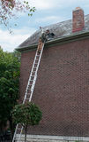 Repairing Slate Roof. Roofing contractor on ladder repairing old slate roof Stock Photos