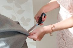 Repairing suit with scissors. As preparation for the wedding Royalty Free Stock Photo