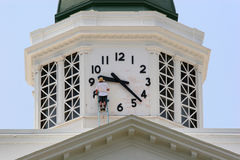 Repairing Time. Man on ladder repairing clock on top of county court house Royalty Free Stock Photos