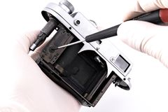 Repairing vintage camera. Vintage analog camera in repairman's hands isolated on white Stock Photography