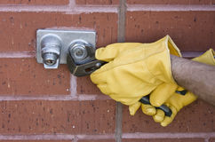 Repairing water faucet. Plumber repairing an outdoor water faucet on a brick wall Stock Photography