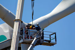 Repairing a wind turbine. Two workers are repairing a wind turbine, crane assisted Royalty Free Stock Image
