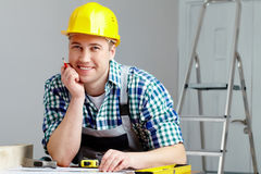 Repairman. Portrait of a cheerful repairman in helmet sitting at table Royalty Free Stock Photo