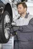 Repairman adjusting car's wheel in workshop Royalty Free Stock Photography
