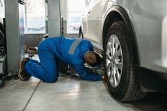 Repairman adjusts lift jack in car service. Repairman in uniform adjusts lift jack in car service, suspension diagnostic. Automobile service, vehicle maintenance stock photography