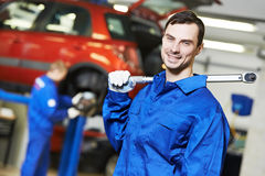 Repairman auto mechanic at work. Young repairman auto mechanic inspecting car during automobile maintenance at engine auto repair shop service station royalty free stock photo