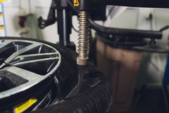 Repairman balances the wheel and installs the tubeless tire of the car on the balancer in the workshop. Repairman balances the wheel and installs the tubeless royalty free stock photos