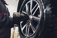 Repairman balances the wheel and installs the tubeless tire of the car on the balancer in the workshop. Repairman balances the wheel and installs the tubeless royalty free stock photo