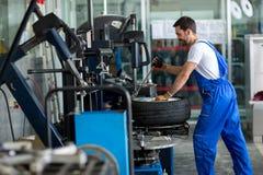 Repairman balancing  car wheel on balancer Royalty Free Stock Images