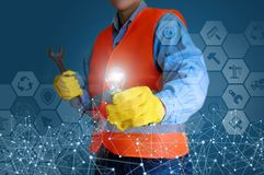 Repairman with a burning light bulb and a monkey wrench. Repairman with a burning light bulb and a monkey wrench on a blue background stock photo