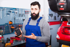 Repairman calculates the cost of a motorcycle repair. Man repairman calculates the cost of a motorcycle repair on the calculator in a workplace Stock Photo