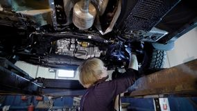 Repairman of car workshop is standing under lifted automobile and examining details, checking backlash in a suspension. Lighting by lantern stock video footage