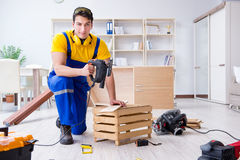Repairman carpenter cutting sawing a wooden board with an electr. Ic power saw Royalty Free Stock Image