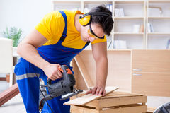 Repairman carpenter cutting sawing a wooden board with an electr. Ic power saw Stock Photography