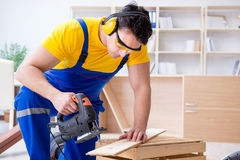 Repairman carpenter cutting sawing a wooden board with an electr. Ic power saw Stock Images