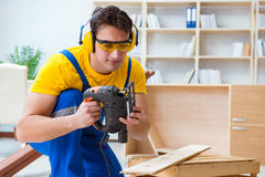 Repairman carpenter cutting sawing a wooden board with an electr. Ic power saw Royalty Free Stock Photo