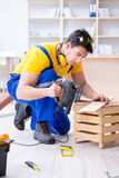 Repairman carpenter cutting sawing a wooden board with an electr. Ic power saw Stock Image