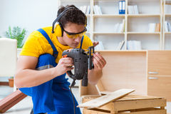Repairman carpenter cutting sawing a wooden board with an electr. Ic power saw Royalty Free Stock Photography