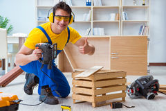 Repairman carpenter cutting sawing a wooden board with an electr. Ic power saw Stock Photo