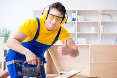 Repairman carpenter cutting sawing a wooden board with an electr Royalty Free Stock Photos