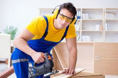 Repairman carpenter cutting sawing a wooden board with an electr. Ic power saw Royalty Free Stock Images