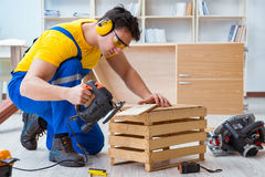 Repairman carpenter cutting sawing a wooden board with an electr. Ic power saw Royalty Free Stock Photos