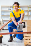 Repairman carpenter cutting sawing a wooden plank with a circula Royalty Free Stock Photos