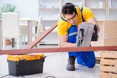 Repairman carpenter cutting sawing a wooden plank with a circula Stock Photos