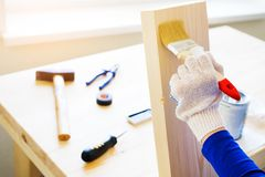 Repairman, carpenter, hired worker applies a protective varnish or paint brush on a wooden Board. Gloved hands, construction tools royalty free stock photography