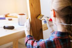 Repairman, carpenter, hired worker applies a protective varnish or paint brush on a wooden Board. Hands in gloves holding a brush stock photography