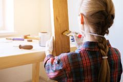 Repairman, carpenter, hired worker applies a protective varnish or paint brush on a wooden Board. Hands in gloves holding a brush stock photos