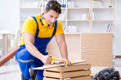 Repairman carpenter working sawing a wooden board with a hand sa. W Royalty Free Stock Photos
