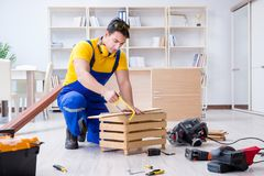 Repairman carpenter working sawing a wooden board with a hand sa. W Royalty Free Stock Photo