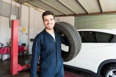 Repairman Carrying Car Tire On Shoulder In Garage. Confident mid adult repairman carrying car tire on shoulder in garage Royalty Free Stock Photography