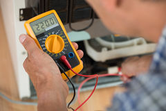 Repairman Checking Fridge With Digital Multimeter. Cropped image of male repairman checking fridge with digital multimeter at home Royalty Free Stock Photos