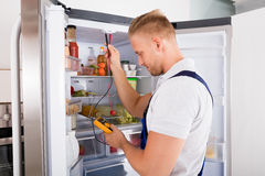 Repairman Checking Refrigerator. Young Repairman Checking Refrigerator With Digital Multimeter Royalty Free Stock Photography