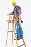 Repairman climbing ladder while holding power drill. Full length portrait of repairman climbing ladder while holding power drill on white background Royalty Free Stock Image
