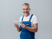 Repairman connecting with a tablet. Confident plumber or mechanic connecting with a digital tablet and using apps royalty free stock photography