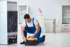 The repairman contractor repairing fridge in diy concept Stock Photography