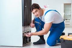 The repairman contractor repairing fridge in diy concept Stock Image