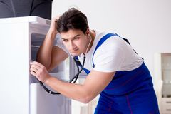 The repairman contractor repairing fridge in diy concept Royalty Free Stock Image