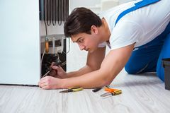 The repairman contractor repairing fridge in diy concept. Repairman contractor repairing fridge in DIY concept Royalty Free Stock Image
