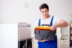 The repairman contractor repairing fridge in diy concept. Repairman contractor repairing fridge in DIY concept Royalty Free Stock Photography