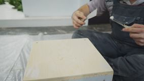 Repairman covers place of screws with construction putty on drawer. stock footage